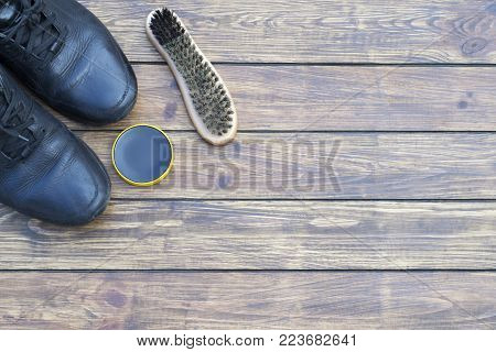 old shabby men's black shoes on laces. shoe polish and a new shoe brush. on a wooden background. top view , place for inscription