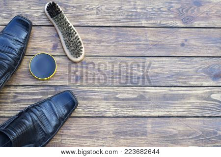 old shabby men's black shoes. shoe polish and a new shoe brush. on a wooden background. view from above