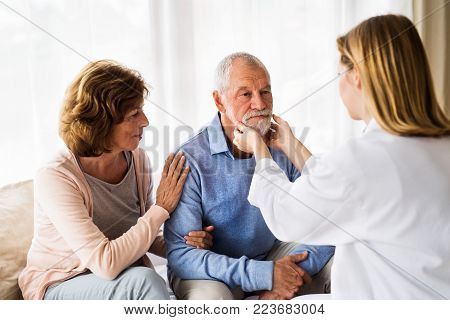 Young female doctor examining a senior man. Senior woman sitting next to man, supporting him.