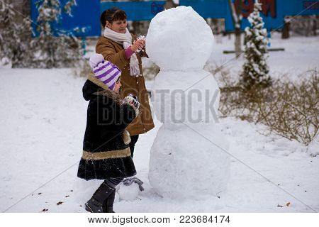 Happy grandmother and little granddaughter sculpt a big real snowman, Happy family play in a winter park