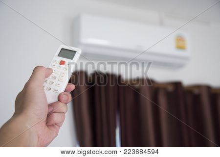 A man use remote controller to set air conditioner temperature in the room.Hand holdind control remote switch of home air conditioner