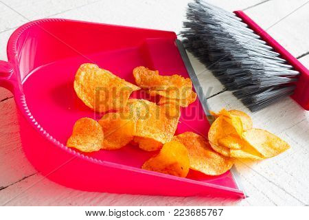 Sweeping junk food with chips and dustpan concept of health detox diet