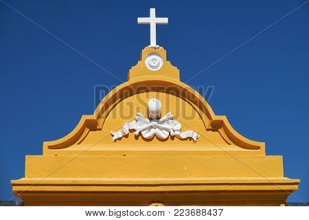 A pediment of cementery gate decorated by the cross and  the Tonenkopf,  a dead's head symbol. Mertola. Portugal.