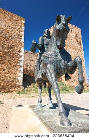 An equestrian statue of Ibn Qasi, the proclaimed political and spiritual leader of the taifa kingdom of Mertola, with the keep tower of Mertola Castle on the background. Mertola. Portugal