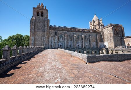 The view of Cathedral (Se) central nave, massive towers,  lantern tower and huge window with Gothic tracery from the roof of the Gothic cloisters. Evora. Portugal.