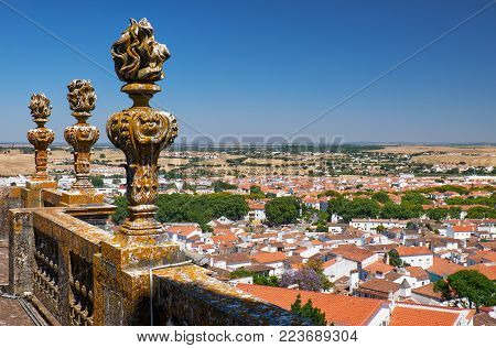 The view of decorative stone torches on the balcony of Evora Cathedral (Se) with the residential city houses and fields on the background. Evora. Portugal