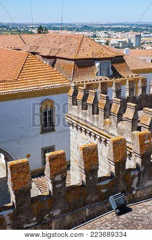 The view of the roof of the Evora Cathedral (Se) decorated with crenellations with the residential houses on the background. Evora. Portugal