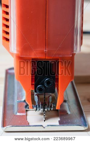 Detail of an orange elctric jig saw