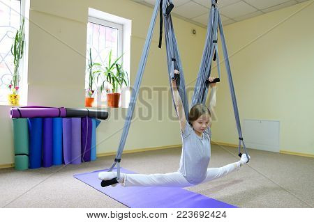 Beautiful girl of American appearance performs acrobatic elements in air, child concentrates and calmly holds on acrobatic ropes. Room nice warm lighting, walls delicate yellow and large windows, on windowsill pots with flowers