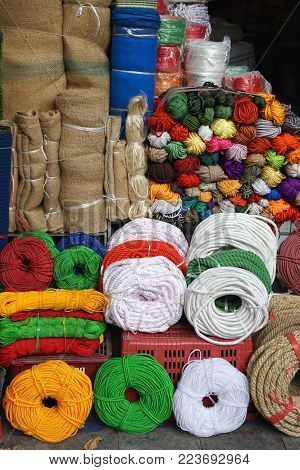 Colorful rolls, hanks, skeins and spools of rope, twine and cord in a market stall in Hanoi Vietnam