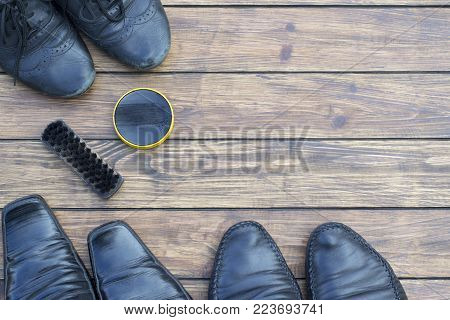three pairs of shabby different shoe of black color, on a wooden background. shoe polish and an old shoe brush. view from above