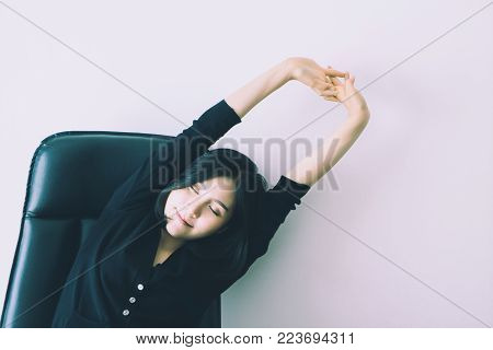 Pretty chinese office worker is stretching arm