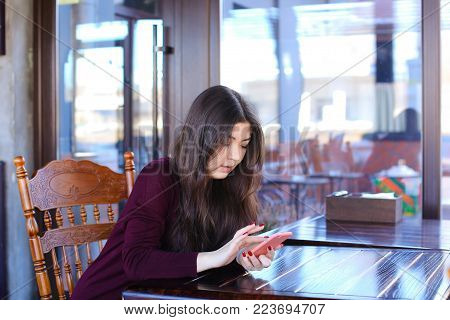 Manicurist replenish mobile account using smartphone and bank card, Asian girl sitting at wooden table near big window in coffee house with antique interior. Young woman with long fair hair and red manicure entering data. Concept of innovative technologie