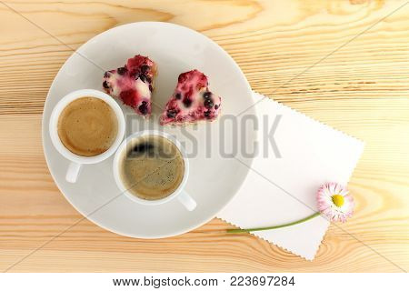 two cups of coffee and a couple of berry cakes in the shape of hearts on plate next to flower / sunny morning breakfast for lovers