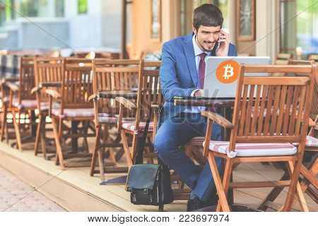 Blockchain technology. Bad news with bitcoin cryptocurrency. Succesful man talk mobile phone. Using laptop. Concept of success
