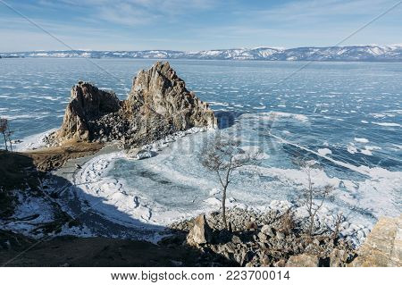 view of rock formations on lake shore over water and hills on background, Russia, Lake Baikal