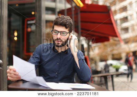 Prosperous businessman speaking with assistant at cafe table and working with documents. Gladden man enjoying achievement. Concept of lucky career in biz and phone conversation.