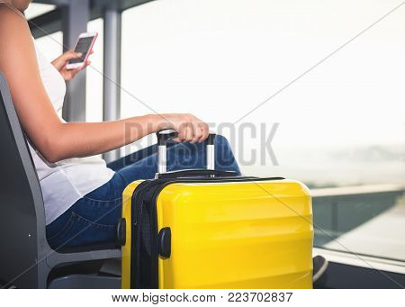 Woman carries your luggage at the airport terminal of Hong Kong, after gonna stady or education fly to Singapore. Use a mobile phone looking for flight