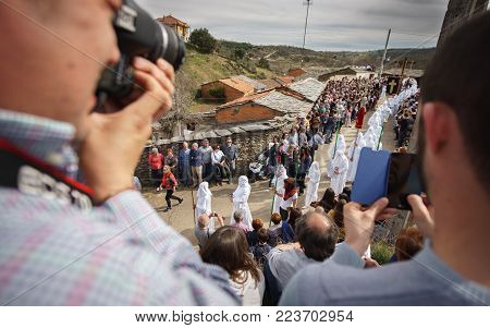 BERCIANOS, SPAIN- APRIL 3, 2015: Unidentified tourists take photos and enjoy the antique brotherhood procession with traditional clothes in Bercianos, Spain
