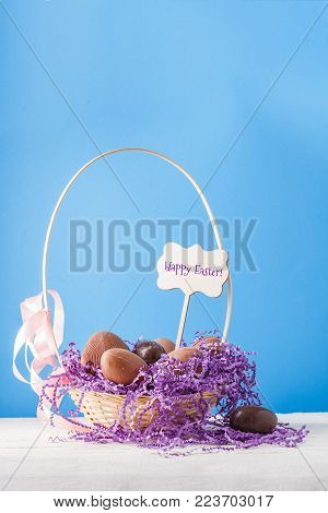 Image of chicken, chocolate eggs, purple decorative paper in basket on empty blue background with wish for happy Easter
