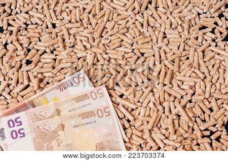 Wood pellets for heating and money.  Money saving concept.