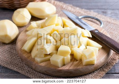 Uncooked cubical yellow potatoes on a chopping board.