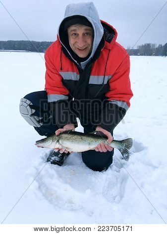 The Adult Man Smiles And Shows The Freshly Caught Pike.