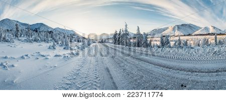 beautiful snow covered winter road and trees in scenic mountains, kolyma highway, russian federation