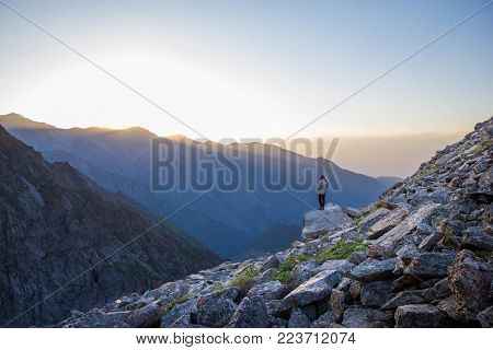 back view of person looking at rocks and beautiful mountains at foggy sunrise, kyrgyzstan, ala archa