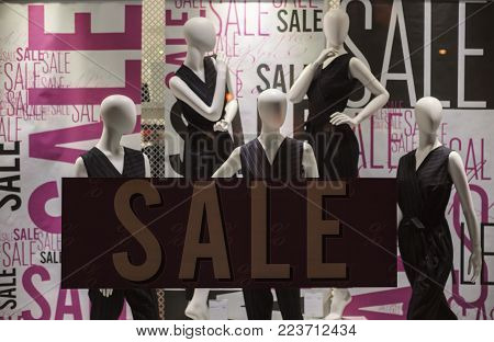 Fashion store window with commercial that big sale is on.