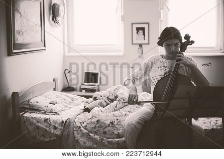 Teenage girl plays cello in her room, in black and white.