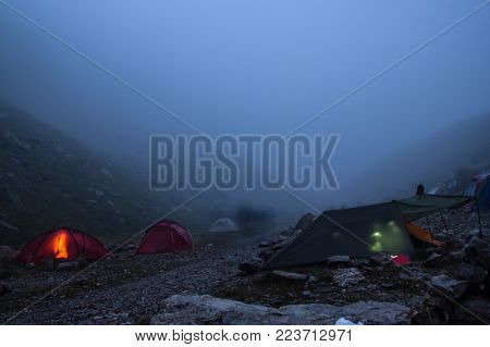 camping with tents and tourists in mountain valley at night and fog, Russian Federation, Caucasus