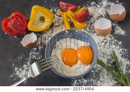 Fresh country eggs . Yolks of eggs in a blue ceramic bowl.  Cooking simple tasty Breakfast.