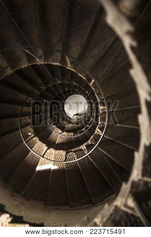 A top to bottom view made from a metal winding staircase inside an old lighthouse in the Red Sea, Egypt. Twisted circles of the spiral stairs look very magnetic.