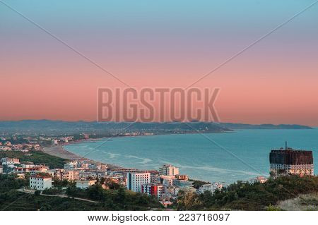 Aerial view to turquoise waters of Adriatic Sea close to Durres in central Albania. Golem zone. Green hills and sandy beach line. Sunset sky