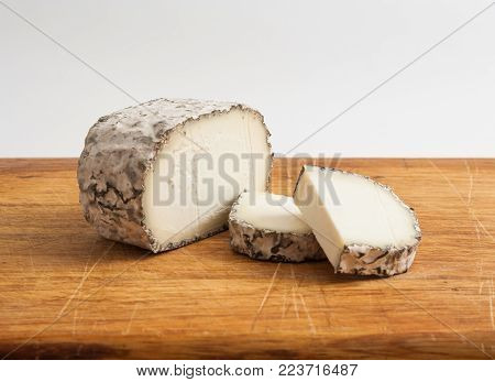 Artisan goat's cheese with mould on a cutting board.