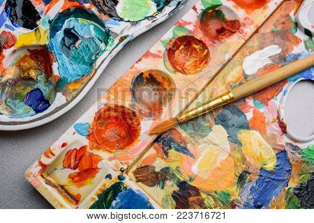 Palette of paints and brush, artist's desk