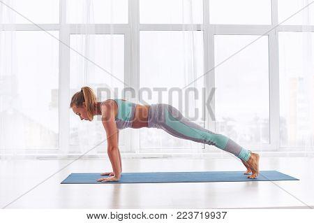 Beautiful woman practices yoga asana Chaturanga Dandasana - four limbed staff pose at the bright yoga class with large windows