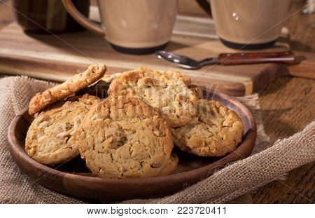Closeup of a pile of peanut butter cookies on a wooden plate