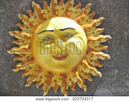 Handmade ceramic yellow symbolic sun of SICILY on wall in city center of TAORMINA with smile and rays in 2016 warm sunny day in Italy, Europe on May.