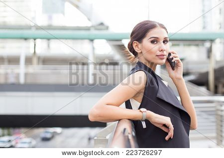 Young Beautiful Business Woman In City Using Smartphone For Work. Young Business Woman With Leader C