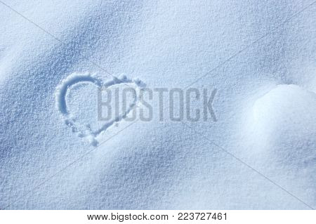 Heart symbol written in the snow, love and Happy Valentine's day concept