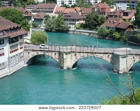 BERN BERNE, SWITZERLAND, bridge over clean alpine Aare river with clean water and cityscape landscape of historical houses on bank in swiss capital city in 2016 warm sunny summer day, EUROPE on JULY