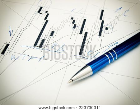 Candlestick forex graph and pencil as usual tools for market analysis.