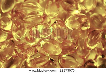Scattering of transparent yellow pills. Background of capsules cod liver oil, omega 3. Advertising a Healthy lifestyle, biologically active additive, dietary nutritional supplements. Horizontal.