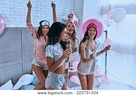 Going crazy. Four attractive young smiling women in pajamas drinking champagne while having a slumber party in the bedroom