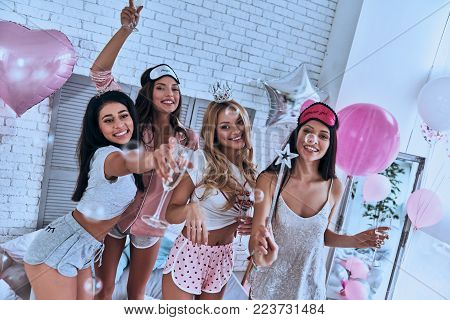 Best party! Four attractive young smiling women in pajamas drinking champagne while having a slumber party in the bedroom