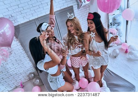 Pajama party. Top view of four attractive young smiling women in pajamas drinking champagne while having a slumber party in the bedroom