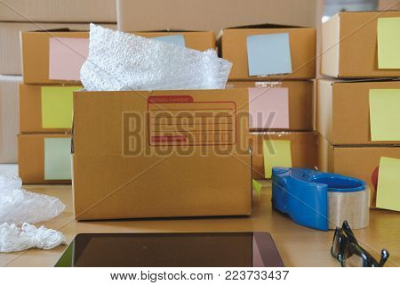 Notebook, Packing Accessories At Workplace Of Startup Small Business Owner. Cardboard Parcel Box For