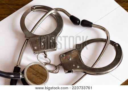Stethoscope and handcuffs on the table concept of medical malpractice